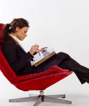 Анна Кастерова в красном кресле с книгой