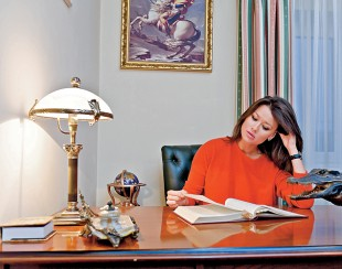 Анна Кастерова за письменным столом читает книгу